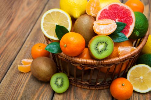 52315233 - fresh juicy citrus fruits in a basket on a wooden background
